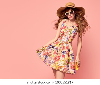 Portrait of Fashion Graceful Young woman in Floral Dress. Pretty Girl in Sunglasses. Slim model in Stylish Summer Attire, living Coral Color. Beautiful Romantic fashionable Lady