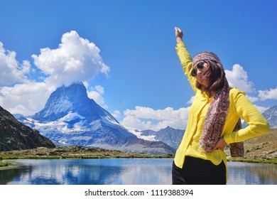 Portrait fashion of Happiness Asian beauty young traveller in action smiling near the alpine lake of Riffelhorn in front of mountain Matterhorn peak, Zermatt, Switzerland.Summer Vacation.