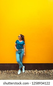 portrait of fashion hipster girl wear sunglasses standing beside wall yellow with posing relaxing smile by wearing blue shirt and blue jeans