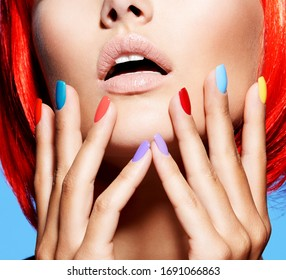Portrait  of a fashion model with bright red color of hairs and multicolor nails. Closeup face of pretty girl with glamour makeup of eyes. Studio photo.