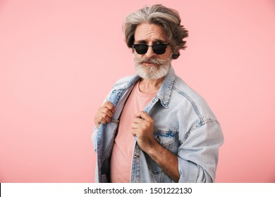Portrait of fashion old man with gray beard wearing sunglasses and denim jacket looking at camera isolated over pink background
