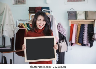 portrait of fashion store owner smiling while holding blank board sign in her shop