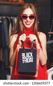 Portrait of fashion successful young woman wearing sunglasses and red dresses showing black friday bag in fashion mall during shopping process, concept of consumerism, Black Friday, sale, rich life