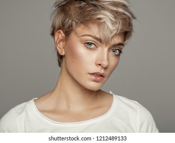 Portrait of fashion trendy haircut girl with copy space isolated on gray background