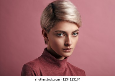Portrait of fashion woman with blond short hair isolated on pink background