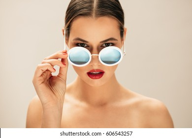 Portrait of fashion woman peeking over sunglasses. Female fashion model posing against beige background.