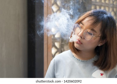 Portrait of fashion woman smoking while wearing glasses against brick wall