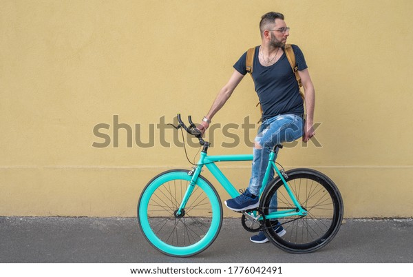 portrait of fashion young cyclist, riding a minimalist bike with yellow wall on background, going from home to work, an ecological and sustainable city transport concept