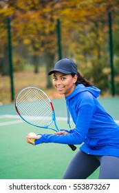 Portrait of fashion young tennis player african girl holding racket outside