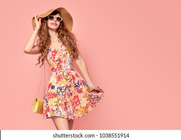 Portrait of Fashion Young woman in Floral Dress. Pretty Girl in Hat, Sunglasses. Female model in Stylish Summer fashionable Outfit. Pink Yellow Vanilla Color. Beautiful Lady. Vintage