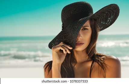 Portrait of fashion young woman wearing a black straw hat. Sensual girl covering half face with hat on beach with copy space. Attractive girl looking at camera with sea in background.