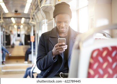 Portrait of fashionable African American student wearing hipster hat and trendy coat checking newsfeed on social networks using smart phone, taking public transport to get to college in the morning