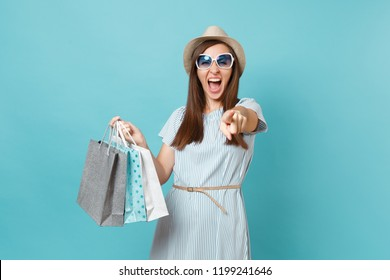 Portrait fashionable attractive happy woman in summer dress, straw hat, sunglasses holding packages bags with purchases after shopping isolated on blue pastel background. Copy space for advertisement
