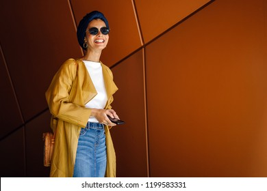 Portrait of a fashionable, attractive Muslim Malay woman in a turban (hijab, head scarf) and sunglasses smiling as she looks up from her smartphone during the day.