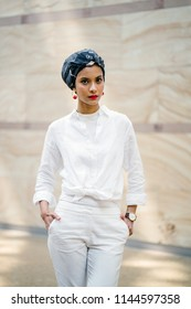 Portrait of a fashionable, attractive, tall and slim Muslim Malay woman. She is wearing a turban head scarf (hijab) and a stylish and fashionable all-white outfit.