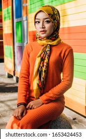 Portrait of a fashionable, attractive, tall and slim Muslim Malay woman. She is wearing a turban head scarf (hijab) and a stylish