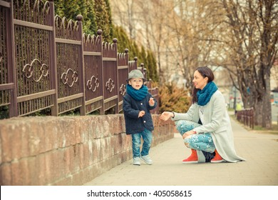 Portrait of fashionable baby boy and his gorgeous mother walking in the street. Happy mother with her son. fashionable mother with young son
