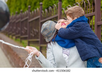 Portrait of fashionable baby boy and his gorgeous mother among balloons. little boy hugs his mother emotionally.