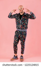 Portrait of fashionable bald odd man in flowered trendy jacket and trousers with pattern isolated on pink background in studio. Cool awesome adult confident atheltic man in fashion clothes and glasses