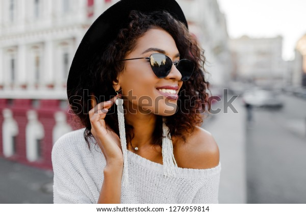 Portrait of Fashionable black woman with stylish Afro hairs posing outdoor. Urban background. Wearing black sunglasses, hat and white earrings. Trendy accessories. Perfect smile.