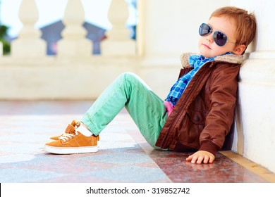 portrait of fashionable boy near the wall