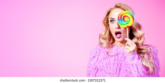 A portrait of a fashionable bright lady posing in studio with colorful lollipop. Fashion for women. Pink colors.