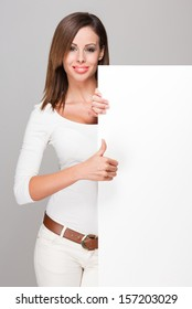 Portrait of a fashionable brunette beauty with blank white billboard for text.