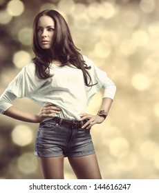 portrait of fashionable brunette girl with smooth hair, casual clothes and denim shorts in fashion pose in bokeh background