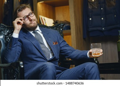 Portrait of fashionable businessman sitting in comfortable leather seat and fixing sliding down glasses with grace. Calm corporation worker holding glass of expensive alcohol