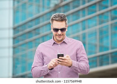 Portrait of fashionable businessman using smartphone outdoors.