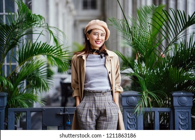 Portrait of a fashionable, elegant and beautiful middle-aged asian woman in the day. She is smiling as she poses for her head shot against green plants in the grey corridor of a court house.