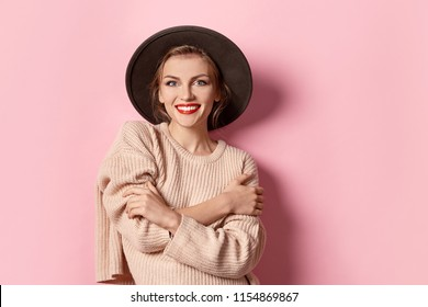 Portrait of fashionable girl wearing light  pullover on pink background. Stunning female with natural makeup and bright red lips. Youth concept.
