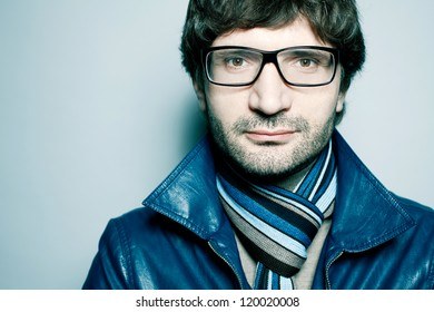 Portrait of a fashionable handsome man in blue jacket with striped scarf over light blue background. Close-up. Copy-space. studio shot