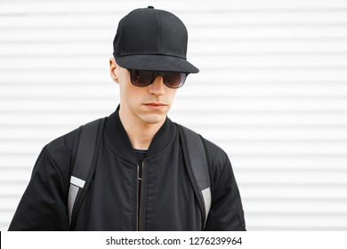 75af55f7ff5b Portrait of a fashionable man hipster in a black cap in stylish black  sunglasses in a