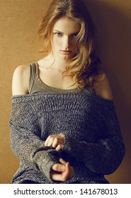 Portrait of a fashionable model with curly red (ginger) hair posing over the wooden background in trendy casual clothes. Seductive glance. Daylight. Studio shot