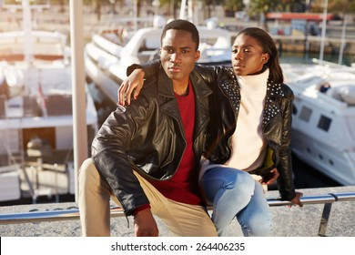 Portrait of fashionable professional couple of models posing outdoors, embracing black couple enjoying time spending together while sitting in yacht port of Barcelona, vacation holidays