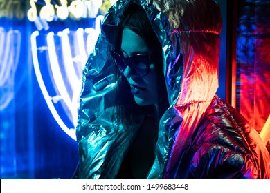 portrait: Fashionable teenager girl in glasses and a shiny jacket sits on a background of neon signs on the street. Neon city lights behind, new generation millennials, Homelander.