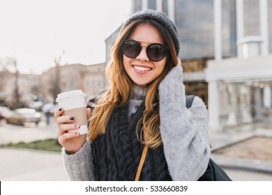 Portrait fashionable urban young woman with coffee to go walking in sunny city centre. Amazing smiling girl in modern sunglasses, knitted hat, woolen sweater having fun outdoor