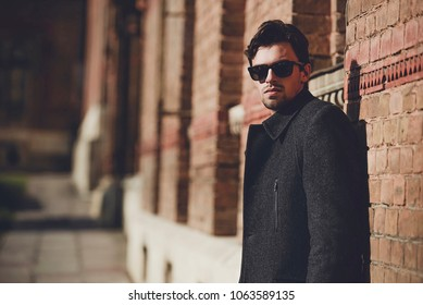 Portrait of fashionable well dressed man with beard posing outdoors looking away, confident and focused mature man in coat standing on a brick wall background, elegant fashion model.
