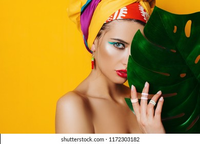 Portrait of a fashionable woman with bright make-up behind a tropical leaf. Yellow background. Beauty, fashion, make-up concept.