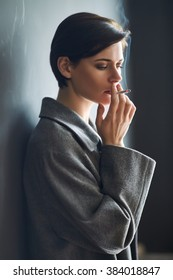 Portrait of fashionable woman smoking a cigarette on dark background