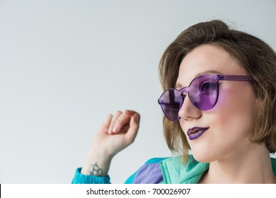 portrait of fashionable woman in sunglasses and vintage clothing isolated on grey