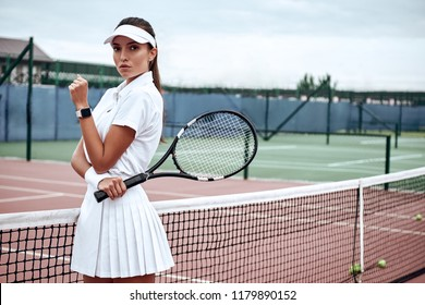 Portrait of fashionable woman in white clothing and cap with tennis racket posing at tennis net on court. Sports Fashion
