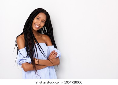 Portrait of fashionable young african woman with braided hairstyle standing with arms crosses against white background