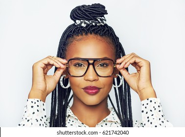 Portrait of fashionable young black woman trying on glasses, white background