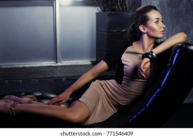 Portrait of a fashionable young elegant woman sitting in a modern chair. Business, elegant businesswoman. Interior, furniture.
