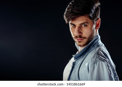 Portrait of a fashionable young man with stylish haircut wearing trendy clothing while posing over black background.