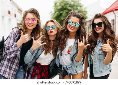 Portrait of fashionable young pretty girlfriends in stylish sunglasses and denim jackets gesturing at camera with thumb up and rock and roll signs and smiling happily in summer street.