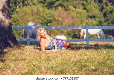 Portrait of fashionable young sensual blonde woman in garden sitting on the grass.