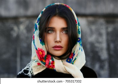 Portrait of fashionable young woman with perfect  make up  posing in colorful Russian shawl on her head, isolated on gray background. Horizontal view.